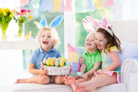 Kids celebrate Easter. Family, happy little girl, boy and baby in bunny ears on a couch. Children having fun on Easter egg hunt. Home decoration, pastel bunny banner, colorful Easter eggs and flowers
