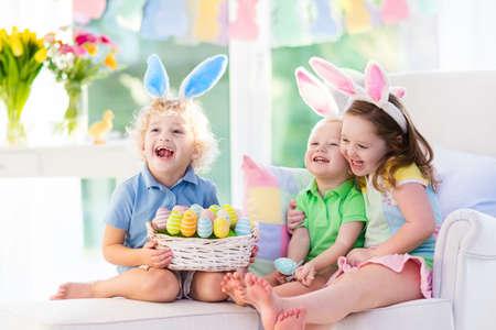 Kinderen vieren Pasen. Familie, gelukkig klein meisje, jongen en baby in bunny oren op een bank. Kinderen vermaken zich tijdens de eieren-jacht op eieren. Woondecoratie, pastel bunny banner, kleurrijke paaseieren en bloemen