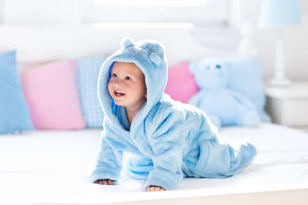 crawl: Cute happy laughing baby boy in soft bathrobe after bath playing on white bed with blue and pink pillows in sunny kids room. Child in clean and dry towel. Wash, infant hygiene, health and skin care.