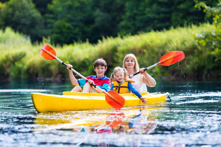 Happy Family With Two Kids Enjoying Kayak Ride On Beautiful River Mother Little Girl