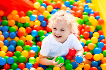 children birthday: Happy laughing boy having fun in ball pit on birthday party in kids amusement park and indoor play center. Child playing with colorful balls in playground ball pool. Activity toys for little kid.