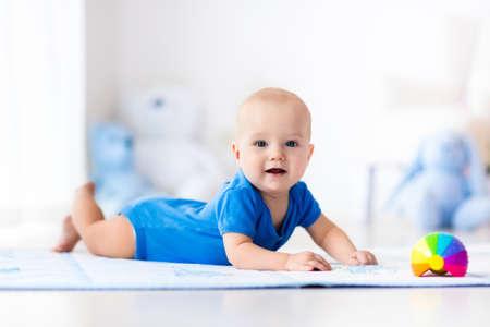 bebes recien nacidos: Adorable bebé aprender a gatear y jugar con el juguete pelota de colores del arco iris en blanco soleado dormitorio. Lindo niño que ríe se arrastra en una alfombra de juego. Cuarto de niños, prendas de vestir y juguetes para niños pequeños.