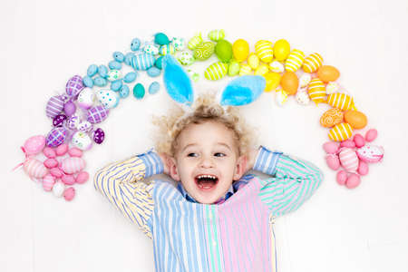 easter eggs: Funny little boy with bunny ears having fun on Easter egg hunt. Child playing with colorful Easter eggs. Kids play with pastel color rainbow eggs. Spring and Easter art and crafts for children.
