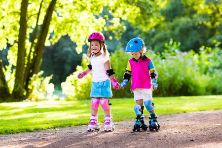 roller blade: Girl and boy learn to roller skate in summer park. Children wearing protection pads and safety helmet for safe roller skating ride. Active outdoor sport for kids. Siblings help and support each other