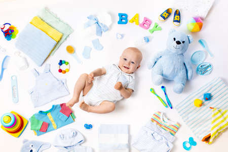 Baby on white background with clothing, toiletries, toys and health care accessories. Wish list or shopping overview for pregnancy and baby shower. View from above. Child feeding, changing and bathing Stock Photo