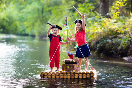 Kids dressed in pirate costumes and hats with treasure chest, spyglasses, and swords playing on wooden raft sailing in a river on hot summer day. Pirates role game for children. Water fun for family. Фото со стока