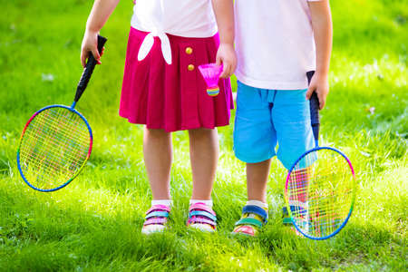 Active preschool girl and boy playing badminton in outdoor court in summer. Kids play tennis. School sports for children. Racquet and shuttlecock sport for child athlete. Kid with racket and shuttle. Stock Photo