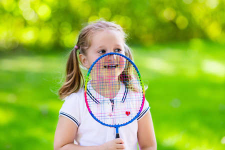 child sport: Active preschool girl playing badminton in outdoor court in summer. Kids play tennis. School sports for children. Racquet and shuttlecock sport for child athlete. Kid with racket and shuttle.