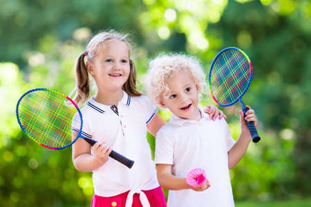 double game: Active preschool girl and boy playing badminton in outdoor court in summer. Kids play tennis. School sports for children. Racquet and shuttlecock sport for child athlete. Kid with racket and shuttle. Stock Photo