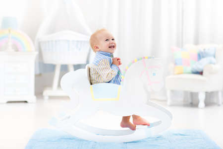Cute baby boy riding wooden traditional rocking horse toy in white bedroom with pastel rainbow color decoration. Child playing in nursery room. Toys for toddler kid. Interior with crib and chair. 版權商用圖片