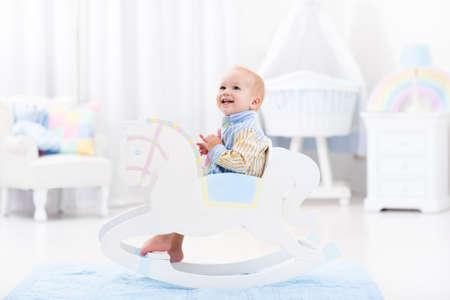 Cute baby boy riding wooden traditional rocking horse toy in white bedroom with pastel rainbow color decoration. Child playing in nursery room. Toys for toddler kid. Interior with crib and chair. Stock Photo