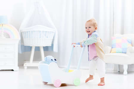 walk in: Baby boy learning to walk with wooden push walker in white bedroom with pastel rainbow color toys. Aid toy for child first steps. Toddler kid walking with car wagon. Nursery interior for baby.