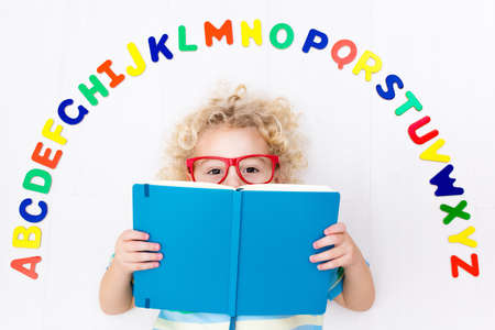 learning by doing: Happy preschool child learning to read and write playing with colorful roman alphabet letters. Educational abc toys and books for kids. School student doing homework. Kid reading in kindergarten.