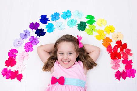 Meisje in roze pastel jurk te kiezen kleurrijke haaraccessoires. Bow en lint voor kinderen. stijl haar en accessoires voor kinderen. Keuze van de bogen. Regenboog linten voor meisjes. Weergave van bovenaf op wit Stockfoto