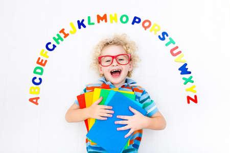 カラフルなアルファベット文字で遊んで読み書きを学んで幸せな幼児。教育 abc おもちゃおよび子供のための本。校生が宿題をしています。子供が幼