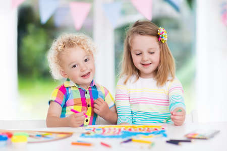 assignments: Little boy and girl draw together in white room with window. Kids doing homework, painting and drawing. Children paint with paintbrush color and pencils. Art and crafts for toddler and preschooler. Stock Photo