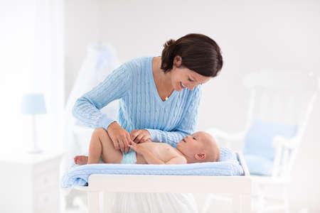 母親と赤ちゃんは、ベッドとロッキングチェア白保育園でお風呂の後おむつを変更します。きれいな乾いたおむつ内のテーブルを変更する小さな男