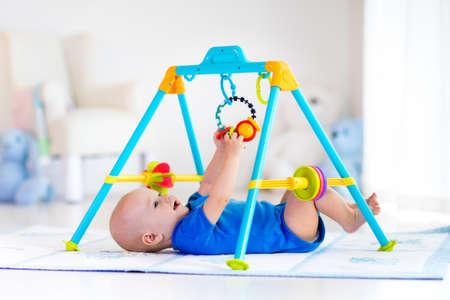 Schattige baby jongen op kleurrijke speelmat en een fitnessruimte, het spelen met opknoping rammelaar speelgoed. Kids activiteit en spelen centrum voor de vroege ontwikkeling van de babies. Pasgeboren kind schoppen en grijpen speelgoed in wit zonnig kwekerij