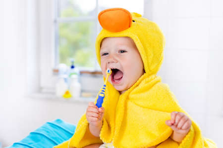 Little baby in yellow duck towel brushing teeth on changing table after bath. Infant boy with tooth brush. Dental hygiene, toothbrush and toothpaste for young kids. Child teeth and oral health care. 版權商用圖片