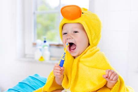 Petit bébé en serviette de canard jaune se brosser les dents sur la table à langer après le bain. Garçon infantile avec une brosse à dents. Hygiène dentaire, brosse à dents et dentifrice pour les jeunes enfants. Dents d'enfant et soins de santé bucco-dentaire. Banque d'images - 72674495