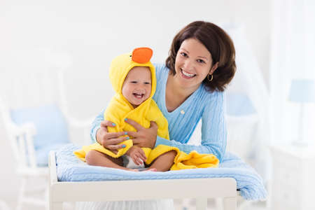 Mother and baby change diaper after bath in white nursery. Little boy in yellow duck hooded towel on changing table in clean dry nappy. Mom taking care of infant child. Kids room interior and hygiene.