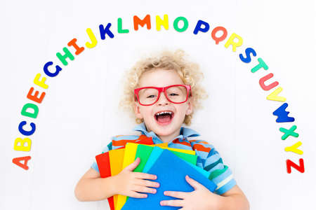 Happy preschool child learning to read and write playing with colorful roman alphabet letters. Educational abc toys and books for kids. School student doing homework. Kid reading in kindergarten.