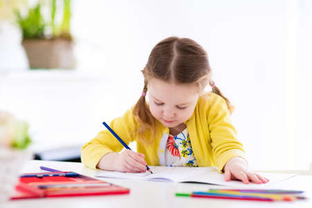 niÑos con libros: Cute little girl doing homework, reading a book, coloring pages, writing and painting. Children paint. Kids draw. Preschooler with books at home. Preschoolers learn to write and read. Creative toddler Foto de archivo