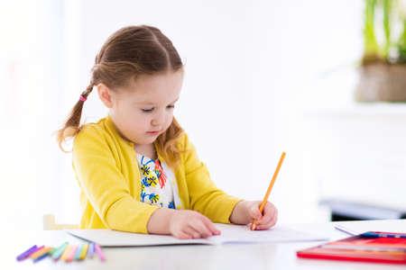 Nette kleine Mädchen Hausaufgaben, ein Buch, Malvorlagen, Schreiben und Malen zu lesen. Kinder malen. Kinder zeichnen. Vorschüler mit Bücher zu Hause. Vorschulkinder lernen zu schreiben und zu lesen. Creative-Kleinkind