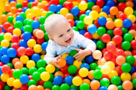 muchacho de risa feliz que se divierte en la piscina de bolas en fiesta de cumpleaños en el parque de atracciones los niños y un centro de juegos interior. Niño que juega con bolas de colores en la piscina de la bola de juego. Los juguetes de actividad para el niño pequeño.