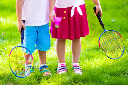 child sport: Active preschool girl and boy playing badminton in outdoor court in summer. Kids play tennis. School sports for children. Racquet and shuttlecock sport for child athlete. Kid with racket and shuttle. Stock Photo