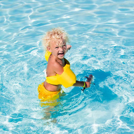 armbands: Happy laughing little boy playing in outdoor swimming pool on a hot summer day. Kids learn to swim. Child with colorful armbands. Family vacation in tropical resort. Stock Photo