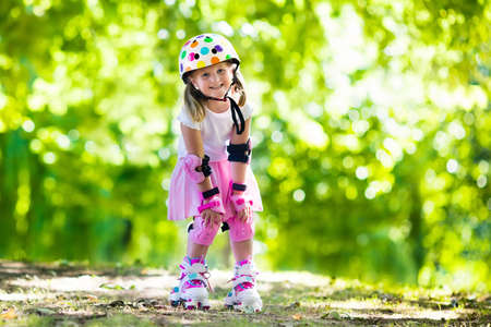 elbow pad: Little girl learning to roller skate in sunny summer park. Child wearing protection elbow and knee pads, wrist guards and safety helmet for safe roller skating ride. Active outdoor sport for kids. Stock Photo