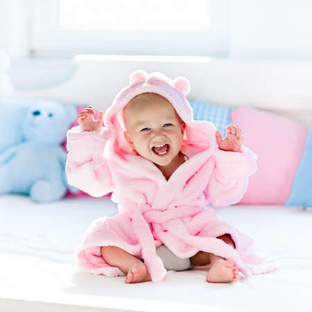 Cute happy laughing baby in soft bathrobe after bath playing on white bed with blue and pink pillows in sunny kids room. Child in clean and dry towel. Wash, infant hygiene, health and skin care. Stock Photo