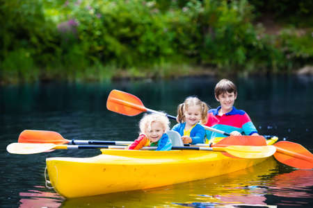 child sport: Happy family with three kids enjoying kayak ride on beautiful river. Little girl, toddler boy and teenager kayaking on hot summer day. Water sport and camping fun. Canoe and boat for children.