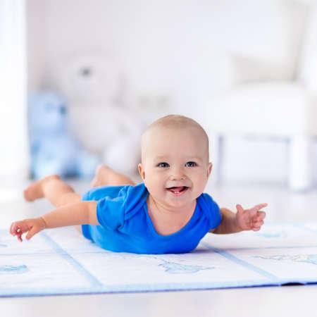 Schattige baby jongen leren kruipen en spelen met kleurrijke speelgoed in het wit zonnige slaapkamer. Cute lachend kind kruipen op een speelmat. Kwekerij interieur, kleding en speelgoed voor kleine kinderen.