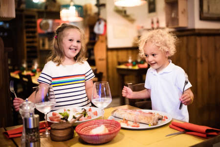 italienisches essen: Kids eat pizza, pasta and salad in traditional restaurant. Eating out with children. Boy and girl having dinner in pizzeria in Italy on vacation in Europe. Italian food and cuisine for family.