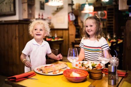 italienisches essen: Kinder essen Pizza, Pasta und Salat in einem traditionellen Restaurant. Essen mit Kindern. Jung und Mädchen, Abendessen in der Pizzeria in Italien im Urlaub in Europa haben. Italienisches Essen und Küche für Familie.