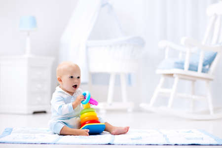 kids toys: Cute baby playing with colorful rainbow toy pyramid sitting on play mat in white sunny bedroom. Toys for little kids. Interior for little boy nursery. Child with educational toy. Early development.