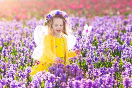 Beautiful girl playing in blooming hyacinth flower field.