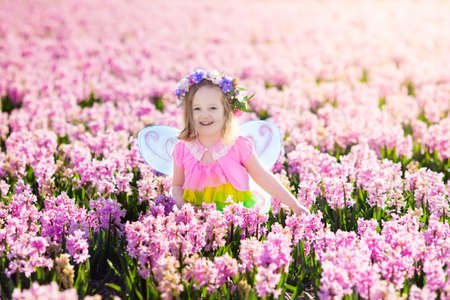 dutch girl: Beautiful girl playing in blooming hyacinth flower field.