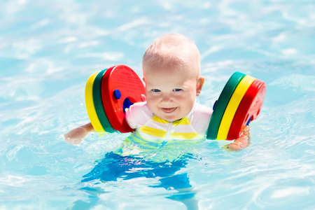 Happy laughing little baby boy playing in outdoor swimming pool on a hot summer day. photo