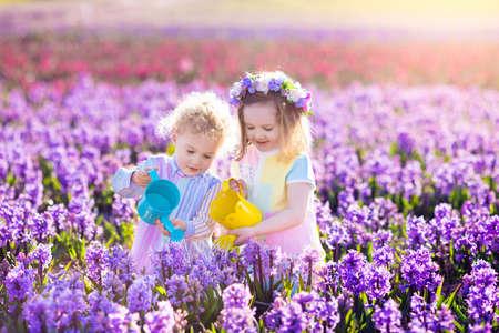 Kinderen planten Lentebloemen in zonnige tuin.