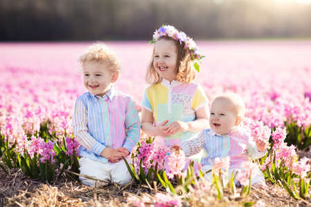 Three children playing in beautiful hyacinth flower field. photo