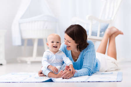 Happy young mother and adorable baby boy playing on a blue floor mat in a white sunny nursery with rocking chair and bassinet. Bedroom interior with infant crib. Mom and child on playmat at kids bed. photo