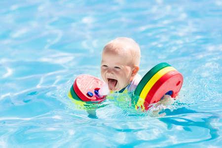 Gelukkige lachende baby jongen spelen in openlucht zwembad op een hete zomerdag. Kinderen leren zwemmen. Kind met kleurrijke floaties. Zwemmen steun voor kind. Familie vakantie in tropisch resort.