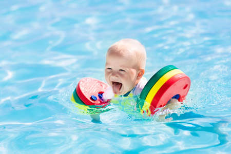 Happy laughing little baby boy playing in outdoor swimming pool on a hot summer day. Kids learn to swim. Child with colorful floaties. Swimming aid for kid. Family vacation in tropical resort. 版權商用圖片
