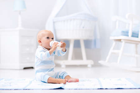Adorable baby boy playing on a blue floor mat and drinking milk from a bottle in a white sunny nursery with rocking chair and bassinet. Bedroom interior with infant crib. Formula drink for infant. photo