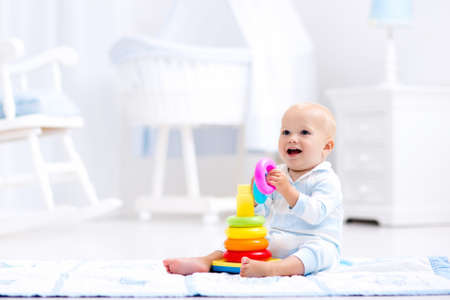 Cute baby playing with colorful rainbow toy pyramid sitting on play mat in white sunny bedroom. Toys for little kids. Interior for little boy nursery. Child with educational toy. Early development.