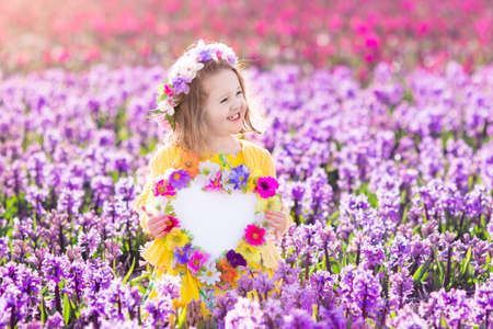Child playing in hyacinth field. Little girl holding a wooden heart shape chalk board standing in a park with spring hyacinths flowers. Copy space for your text. Happy mothers day card.