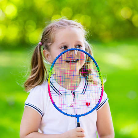shuttlecock: Active preschool girl playing badminton in outdoor court in summer. Kids play tennis. School sports for children. Racquet and shuttlecock sport for child athlete. Kid with racket and shuttle.